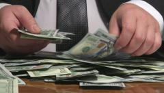 Business person sorting US 100 dollars bank notes at desk Stock Footage