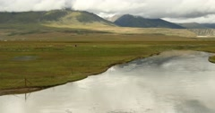 4k clouds mass rolling over Tibet mountain,River flowing the prairie Stock Footage