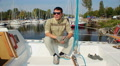 Portrait of positive young man on sailboat in marina, yachting Footage