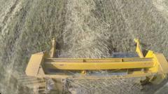 A combine harvester (header) harvesting an oats crop - stock footage