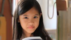 Close up little Asian girl reading a book in library Stock Footage