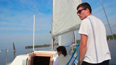 Male and female sailors navigate sailing yacht. Making a turn Stock Footage