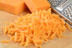 Grated cheese on a cutting board Stock Photos