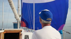 Gray-haired captain giving orders to crew on sailing yacht Stock Footage