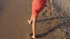 Mother with little daughter walking along the seashore leaving footprints on the Stock Footage