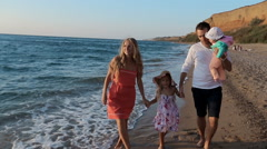 Father, mother , little girl and baby walking along the beach in slow motion - stock footage