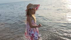 Little cute girl in sundress and straw hat standing knee-deep in sea water Stock Footage