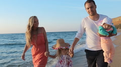 Friendly family walking along the coast in slow motion Stock Footage