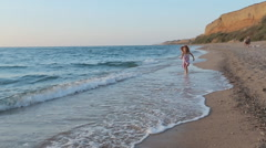 Little girl in sundress running along the sea to father and he lifts her up in Stock Footage