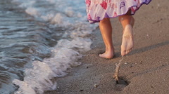 Little girl runing along the beach in sundress in slow motion back view - stock footage