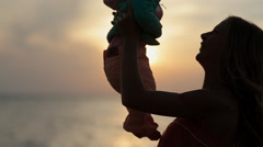 Silhouettes of father and mother with baby at sunset near the sea in slow motion Stock Footage