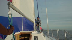 Captain putting up mainsail on beautiful yacht, traveling Stock Footage