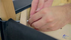 Screwing leg to chair close up Stock Footage