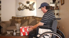 DISABLED-PARAPLEGIC AND PRESENT: old man with gift in wheelchair Stock Footage