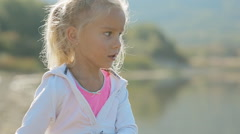 Adorable little girl in bright pink skirt throwing stones into the water of the Stock Footage