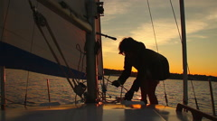 Woman sailor working on sailboat at sunset, hobby, active rest Stock Footage