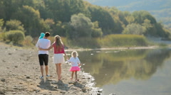 United family with two young children walking along the lake view from the back - stock footage
