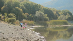 Happy family with two young daughters walking along the lake - stock footage