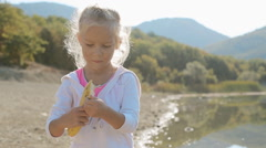 Portrait of little blond girl who eats banana while standing next to lake Stock Footage