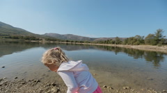 Little girl with ponytail throws stone into lake in slow motion Stock Footage