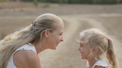 Beautiful mother with little daughter laugh and rejoice in the field Stock Footage