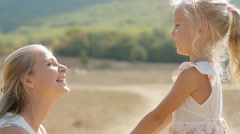 Close up of mother and little daughter embracing and laughing in the middle of Stock Footage