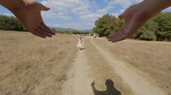 Carefree little girl is twirled around by father in the field Stock Footage