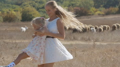 Young mother whirling her little daughter next to the flock of sheep in slow Stock Footage