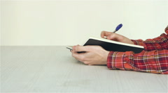 A guy writes notes in a notebook with a pen on a table Stock Footage