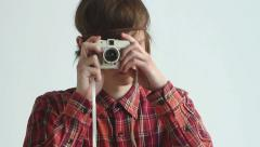 A guy in a shirt takes pictures with a lomo camera at white background Stock Footage