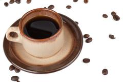 Coffee cup and scattered beans Stock Photos