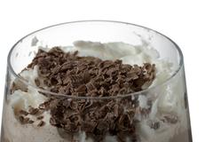 A glass of chocolate milk drink with cream and chocolate bits Stock Photos