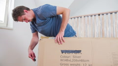 Man unpacking big box with knife - stock footage