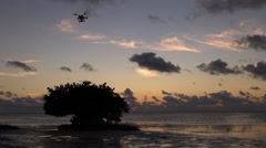 A DJI Phantom 2 quadcopter drone hovers at dawn Stock Footage