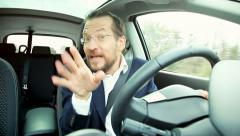 Funny business man singing in car looking in camera Stock Footage