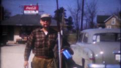 1534 - a sportsman gathers his gear from the car - vintage film home movie Stock Footage