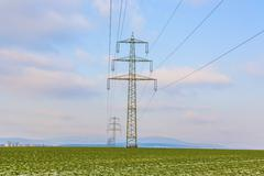 Acres with snow in winter with electricity tower in sunset Stock Photos