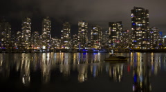 Vancouver condos time lapse at night. False creek and boat in the foreground. Stock Footage