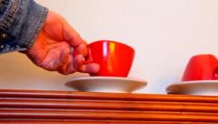 Man's hand in a blue denim shirt upends red cup on saucer Stock Footage