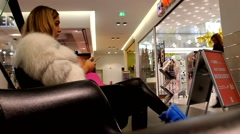 Young woman in a fur coat at Christmas sales in a large department store - stock footage