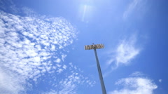Stadium spot lights, beautiful blue sky and clouds running background. Stock Footage