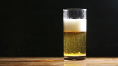 Beer bubbles float in cold ice glass on wood desk and black background Stock Footage