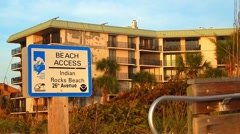 Beach access sign next to resort Stock Footage