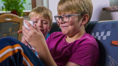 Stock Video Footage of Young kid annoying older brother while playing with smartphone