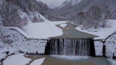 Aerial - Small waterfall of a river in a snow covered mountain region Stock Footage