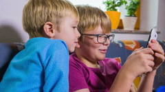 Child interested in what brother is playing on smartphone - stock footage
