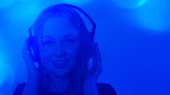 Attractive young woman listening to music, blue background - stock footage