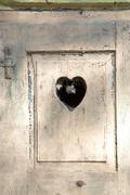 Stock Photo of old wooden door in meran, tirol, italy with a carved romantic heart