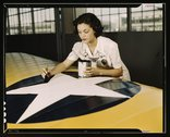 Painting the American insignia on airplane wings is a job that Mrs Stock Photos