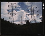 Transmission line towers and high tension lines that carry current generated  Stock Photos